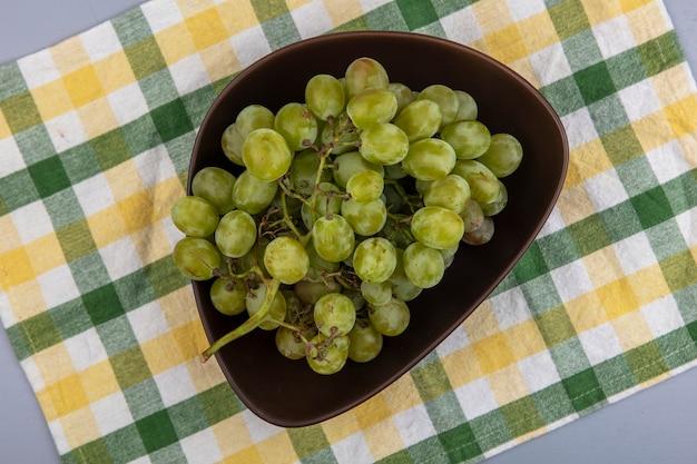Вид сверху белого винограда в миске на клетчатой ткани на сером фоне