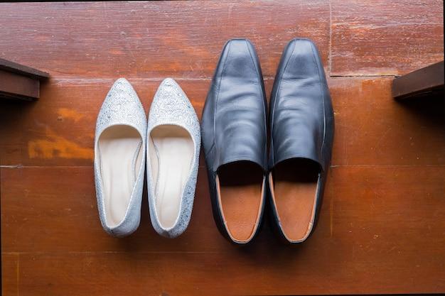 木製の背景に白いハイヒールと男性の靴のトップビュー