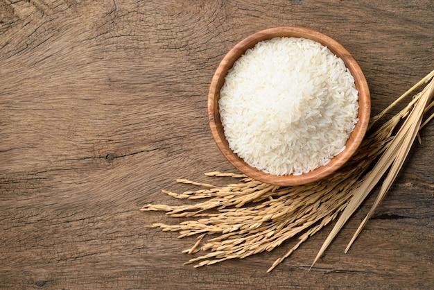 나무 배경에 논 쌀 귀와 화이트 재스민 쌀의 상위 뷰