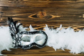 Top view of white masquerade carnival mask with boa feather on wooden textured background