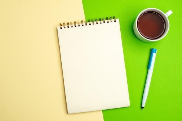 흰색과 노란색 배경에 차 한 잔 옆에 펜이 있는 흰색 노트북의 상위 뷰