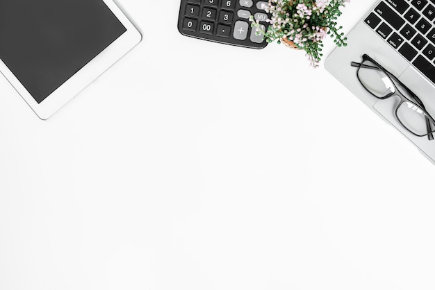 Вид сверху на белый офисный стол с большим количеством вещей на нем. компьютерная клавиатура и другие офисные принадлежности.