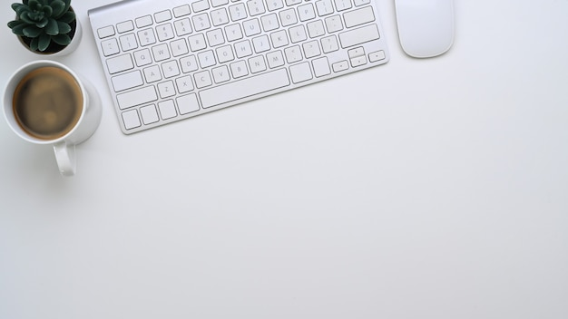 Взгляд сверху белой клавиатуры остроумия офисного стола, кофейной чашки и космоса экземпляра.
