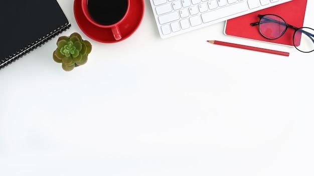 Вид сверху белого офисного стола с клавиатурой, кофейной чашкой, тетрадью и копией пространства.