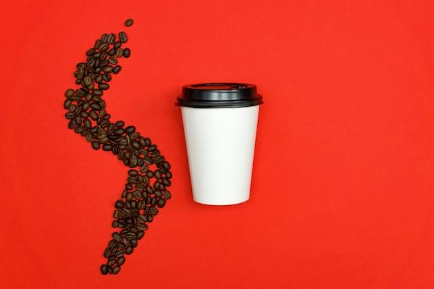 Взгляд сверху кофейной чашки белой бумаги устранимой на красной предпосылке с кофейными зернами.