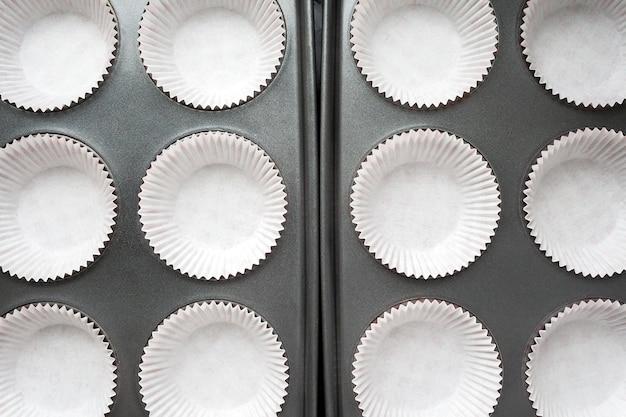Вид сверху на белые бумажные обертки для кексов в форме для выпечки