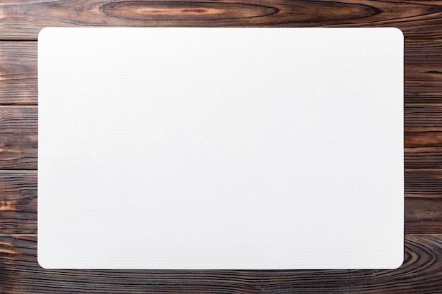 Взгляд сверху белой циновки места для блюда. деревянный стол