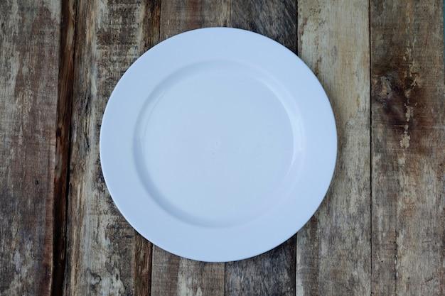 Вид сверху белой тарелки на деревянном фоне