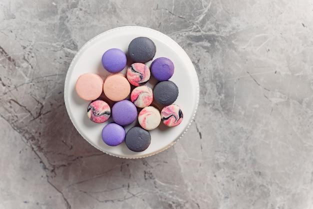 Взгляд сверху белой плиты с покрашенными macarons на мраморной таблице. вкусный десерт.