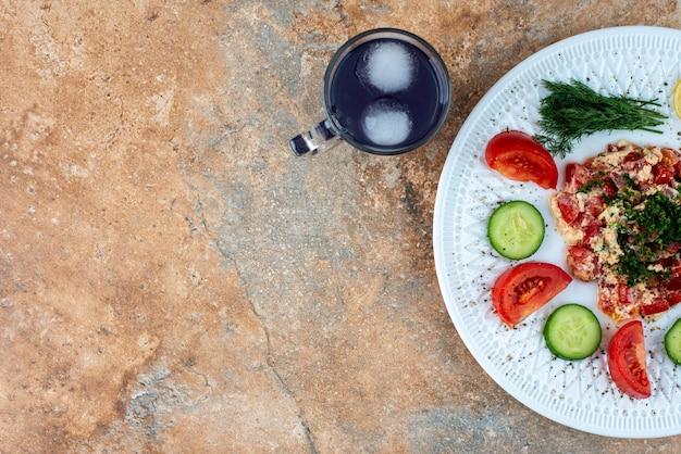 Вид сверху белой тарелки с овощами и стаканом сока.