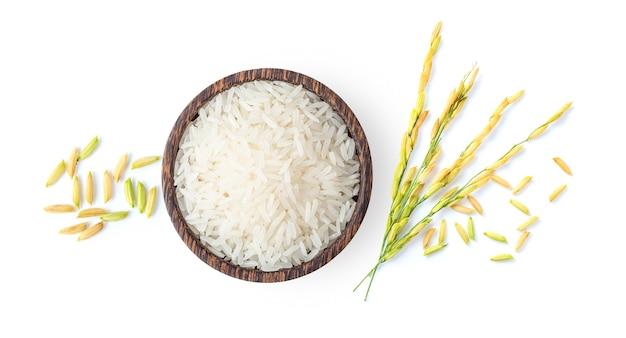 흰 배경에 고립 된 쌀 귀가 있는 나무 그릇에 있는 흰 쌀과 논 쌀의 상위 뷰