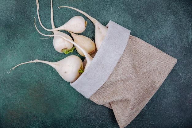 緑の表面の黄麻布の袋に白い根菜ビートルートの上面図