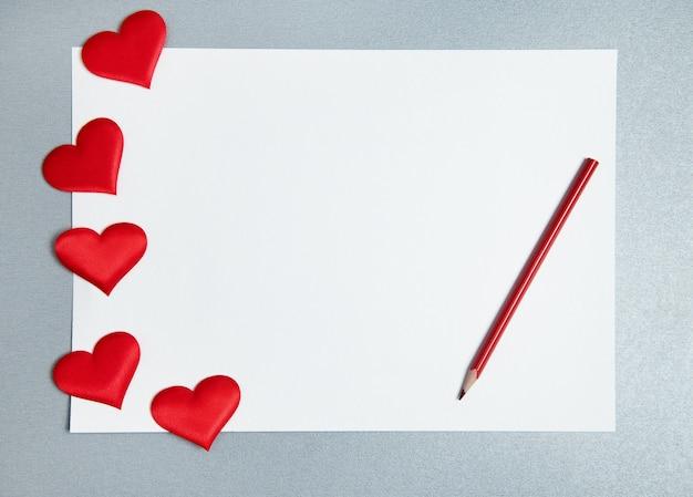 Вид сверху белого листа бумаги, красного карандаша и распространенных сердец на сером фоне. концепция дня святого валентина. копировать пространство