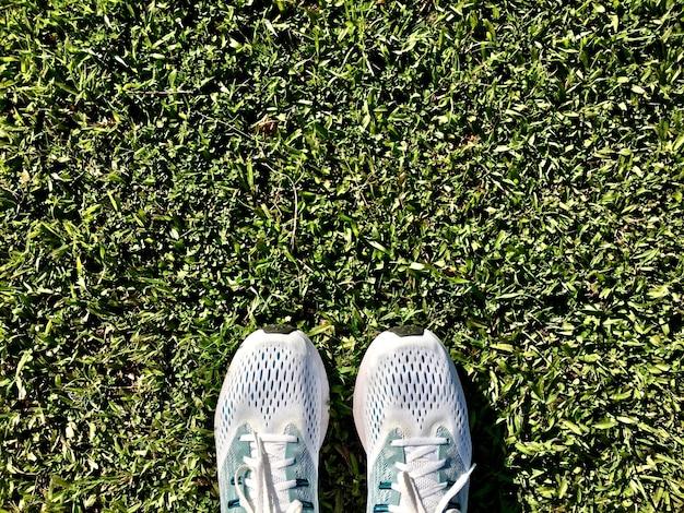 푸른 잔디에서 남자의 실행에 사용되는 흰색 신발의 상위 뷰 프리미엄 사진