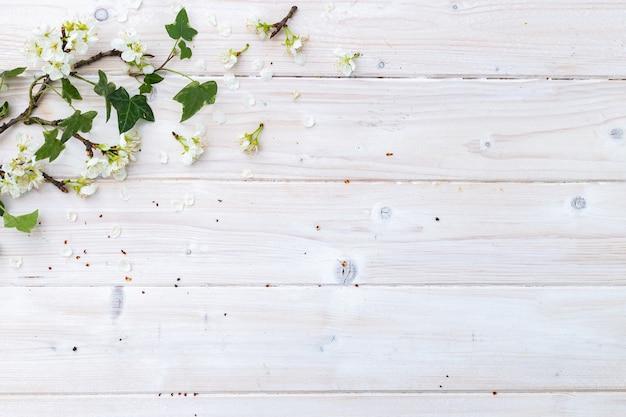 あなたのテキストのためのスペースと木製のテーブルの上の白い春の花と葉の上面図