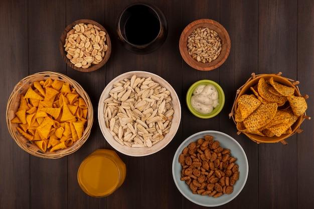 Вид сверху белых семечек на миске с острыми чипсами на ведре с кукурузными закусками на ведре с кедровыми орехами на деревянной миске с соусом на зеленой миске на деревянном столе
