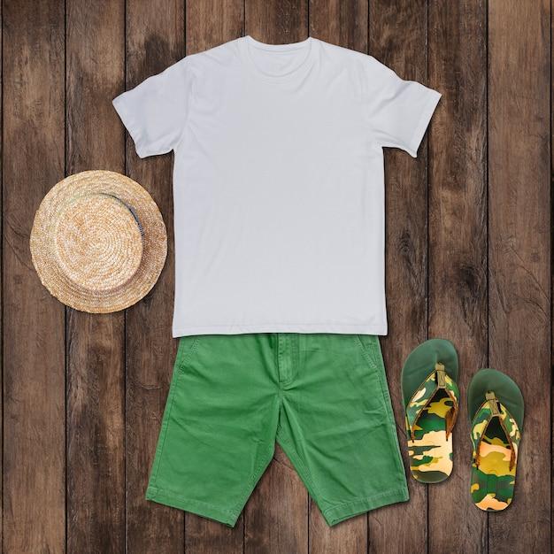 緑のショートパンツ、サンダル、帽子が木の床に置かれた白いtシャツの上面図。
