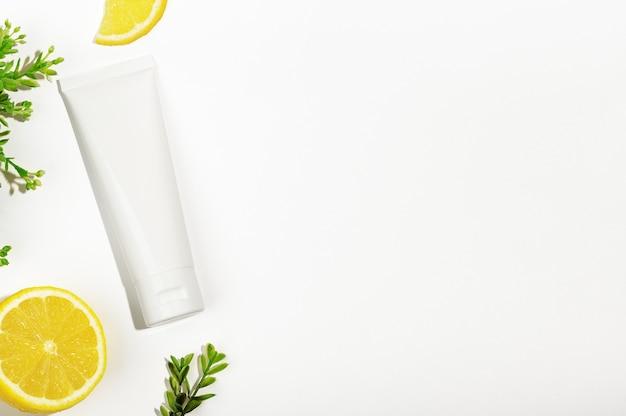 Вид сверху на белую трубку других производителей с зеленым растением и сочным лимоном. пустой флакон для натуральной косметики. емкость для питательного крема, скраба для тела, лосьона или солнцезащитного крема. органическая косметология.