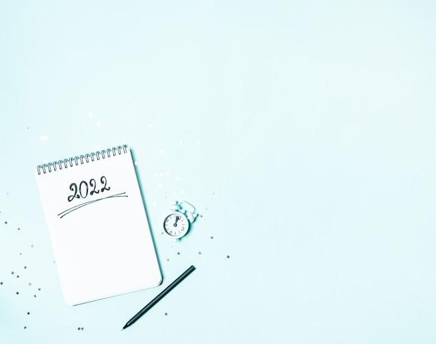 Вид сверху на белый винтажный будильник и пустой блокнот, готовый к планированию нового 2022 года или списку желаний