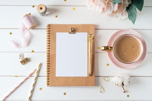 Взгляд сверху белой предпосылки рабочего стола с тетрадью чистого листа бумаги, чашкой кофе. плоская планировка