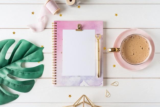 Взгляд сверху белого рабочего стола с тетрадью чистого листа бумаги, чашкой кофе. плоский лист монстеры, золотые зажимы для бумаги. блокнот и ручка.