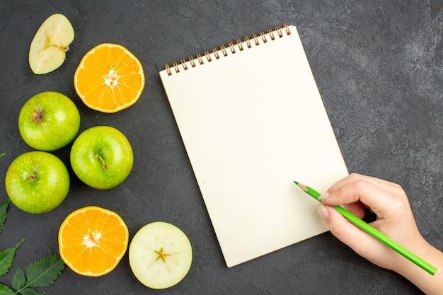 검정 배경에 펜이 있는 노트북 옆에 전체 및 잘게 잘린 신선한 녹색 사과와 민트 컷 오렌지의 상단 보기