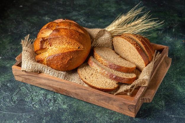 Вид сверху целого и нарезанного свежего черного хлеба на полотенце в коричневой деревянной коробке на поверхности темных цветов