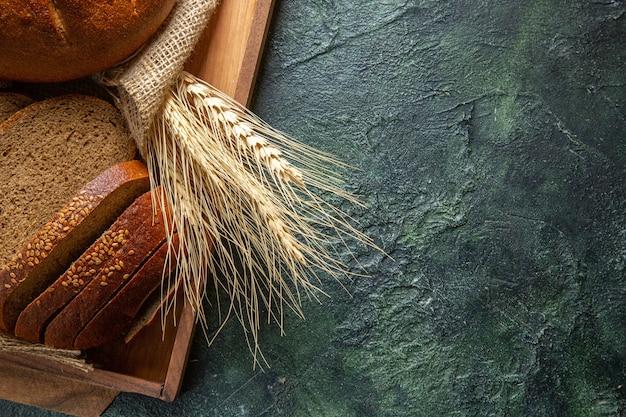 Вид сверху целого и нарезанного свежего черного хлеба на полотенце в коричневом деревянном подносе на фоне темных цветов
