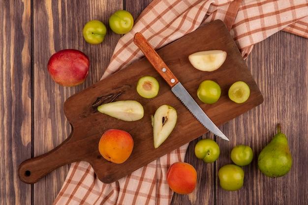 Вид сверху целых и нарезанных фруктов в виде слива абрикосовой груши с ножом на разделочной доске на клетчатой ткани и рисунком из персика, сливы, груши, абрикоса на деревянном фоне