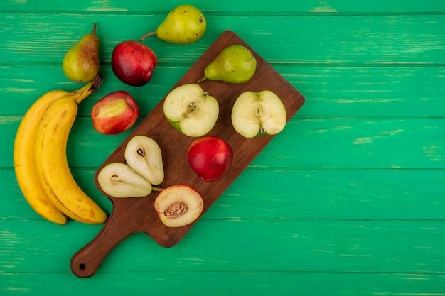 コピースペースと緑の背景にバナナとまな板の上の梨リンゴ桃として全体と半分カットフルーツのトップビュー