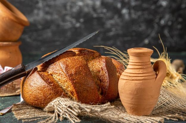 어두운 벽에 갈색 수건 도자기에 전체 검은 빵의 상위 뷰