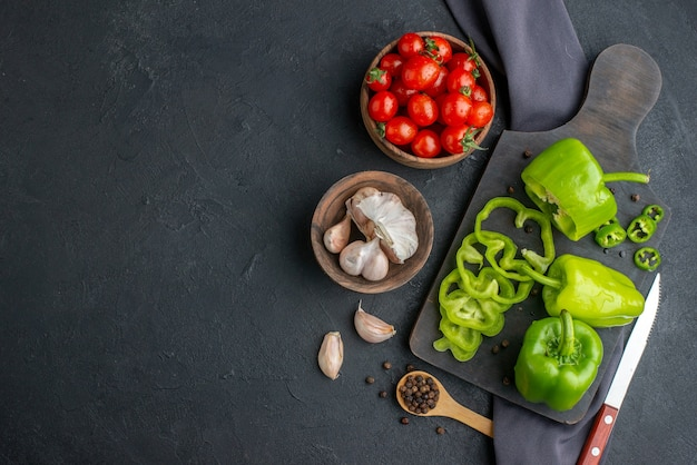 黒い表面の左側にある濃い色のタオルの上にボウルのニンニクの木製まな板トマトの全体のカットみじん切りピーマンの上面図