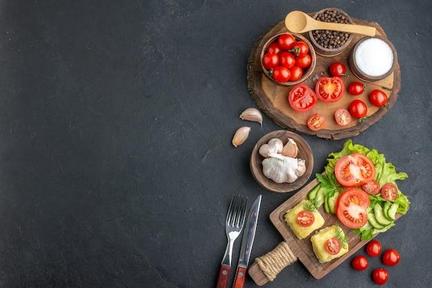 Вид сверху целых нарезанных свежих овощей и специй на деревянной доске с белым полотенцем, ножом, сыром на черной поверхности