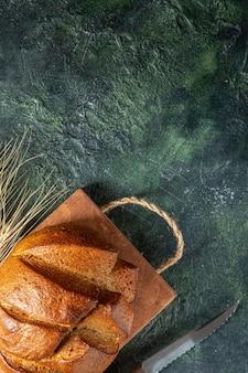 어두운 색상 표면에 갈색 나무 커팅 보드 칼에 전체 신선한 검은 빵의 상위 뷰