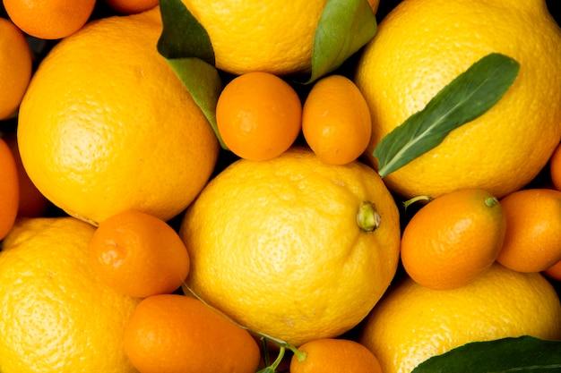 Вид сверху целых лимонов и кумкватов