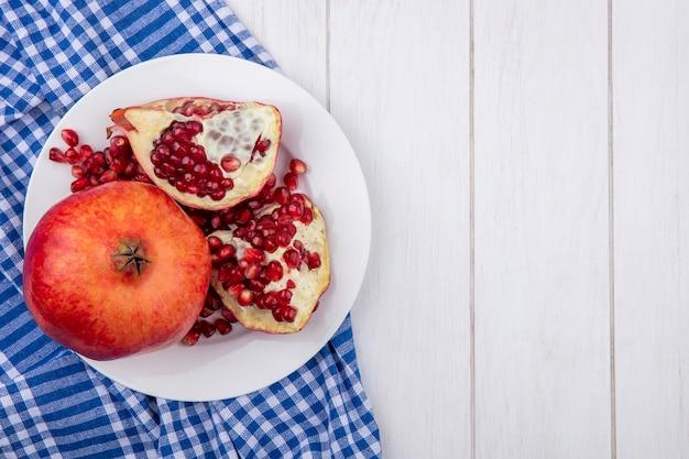 Вид сверху целых кусочков граната и граната с ягодами в тарелке на клетчатой ткани и деревянной поверхности