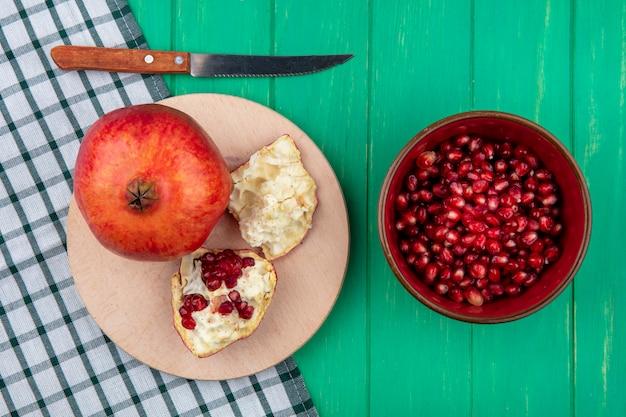 緑の表面にザクロの果実のボウルとまな板の上の部分と格子縞の布の上のナイフでザクロ全体の平面図