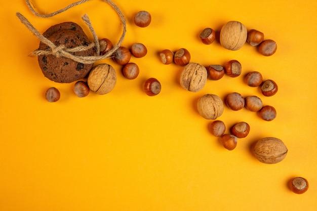 Вид сверху целых грецких орехов и фундука и овсяного печенья, перевязанного веревкой на желтом