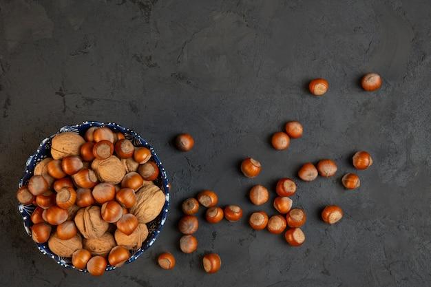 Вид сверху целых грецких орехов и фундука в миску на темном j