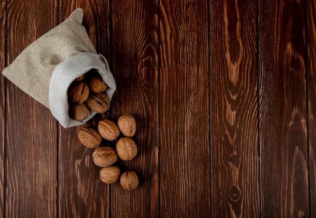 Взгляд сверху всех грецких орехов разбросанных от мешка на деревянной предпосылке с космосом экземпляра
