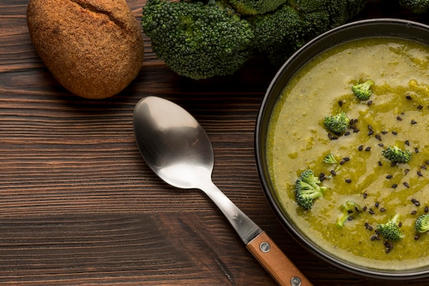 Вид сверху зимний суп из брокколи с ложкой и хлебом