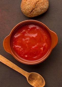 Вид сверху на зимний томатный суп в миске с хлебом и ложкой