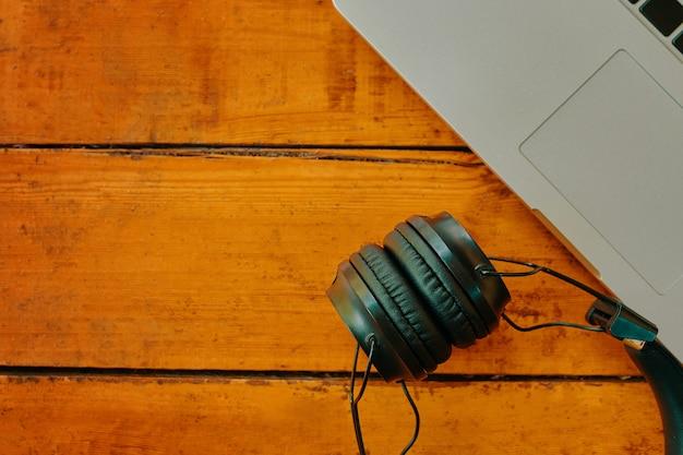 나무 테이블 복사 공간에 있는 무선 헤드폰 및 노트북 키보드 현대적인 가제트의 상위 뷰...