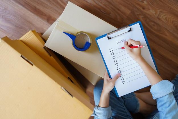商品のパッケージをチェックまたは配達または出荷前に梱包し、チェックリストで新しい家に移動する準備をする女性のトップビュー