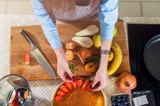 딸기 케이크 레이어를 장식하는 여자의 상위 뷰. 과일 파이 요리하는 주부