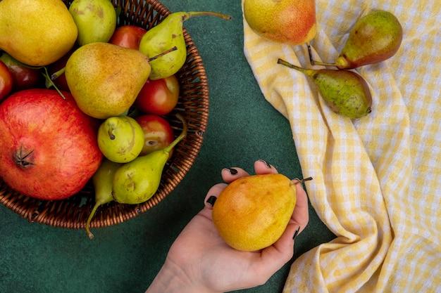 Взгляд сверху руки женщины держа персик с корзиной сливы персика гранатового дерева на зеленой поверхности