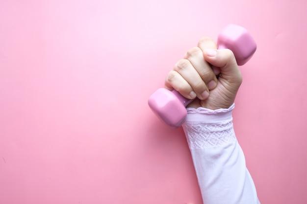 ピンクのダンベルを持っている女性の手の上面図。