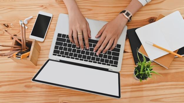Взгляд сверху руки женщины пока использующ / печатающ на черной компьтер-книжке пустого экрана включая держатель карандаша, черный smartphone пустого экрана, в горшке завод, карандаш, примечания, наушник на деревянном столе.