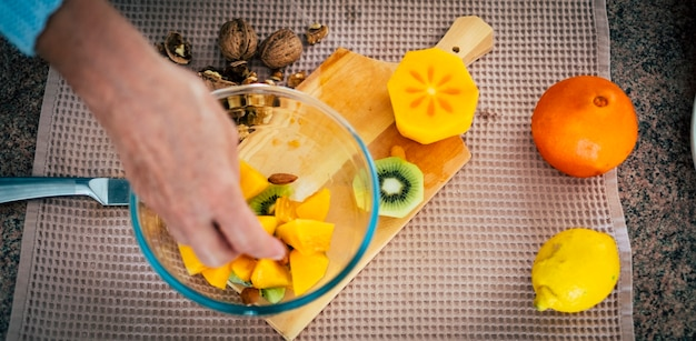 Вид сверху руки женщины, режущие свежие апельсины ножом. женщина делает салат из свежих фруктов. вегетарианская концепция - изображение