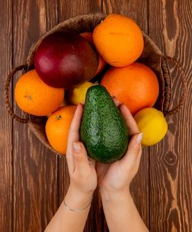 木製のテーブル上のバスケットにアボカドマンゴーレモンオレンジとしてアボカドと柑橘系の果物を保持している女性の手の上から見る